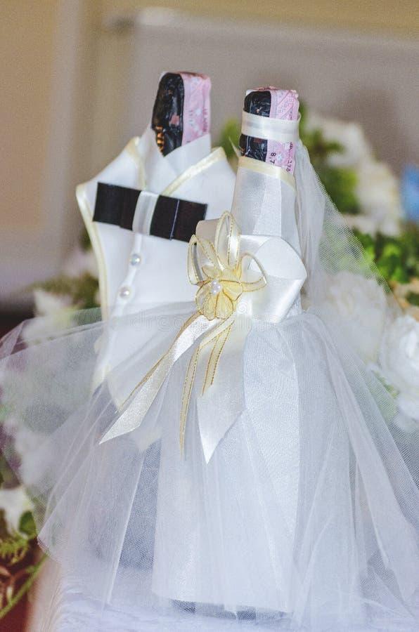 Garrafas do champanhe em um vestido dos noivos foto de stock royalty free