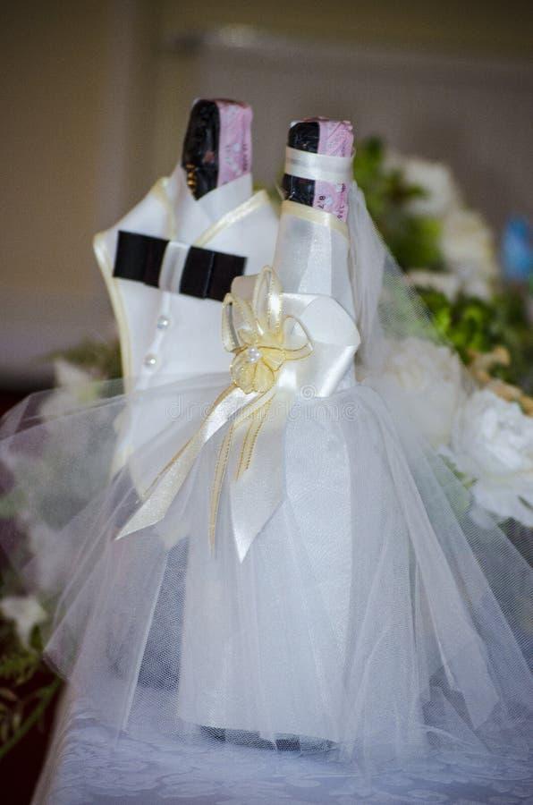 Garrafas do champanhe em um vestido dos noivos imagem de stock