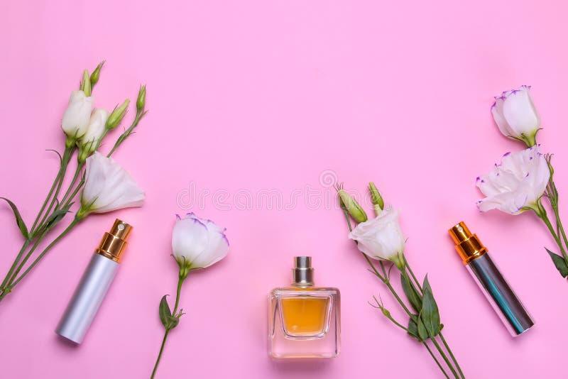 Garrafas do perfume e do eustoma bonito das flores em um fundo cor-de-rosa brilhante Acessórios do ` s das mulheres Vista superio foto de stock royalty free