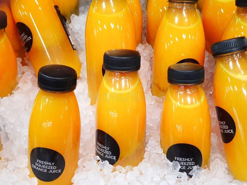 Garrafas do suco de laranja fresco saudável na exposição sentada no gelo profundo imagens de stock