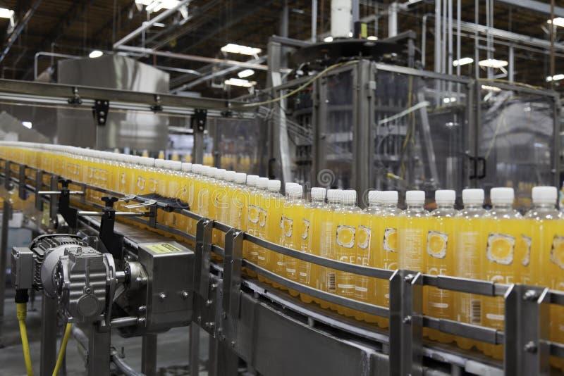 Garrafas do suco de laranja no transporte na planta de engarrafamento fotografia de stock royalty free