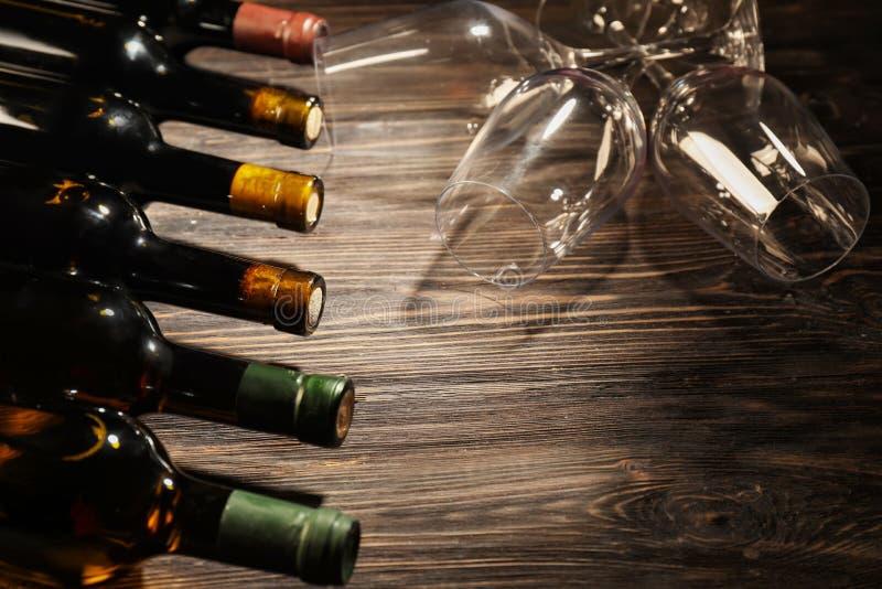 Garrafas do vinho diferente e de vidros vazios na tabela de madeira imagens de stock