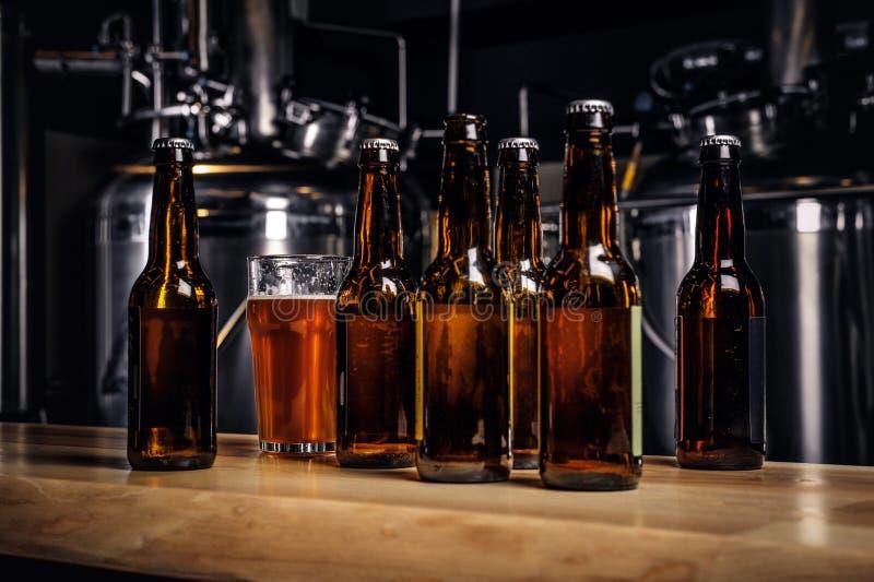 Garrafas e vidro da cerveja do ofício no contador de madeira da barra na cervejaria indie imagens de stock