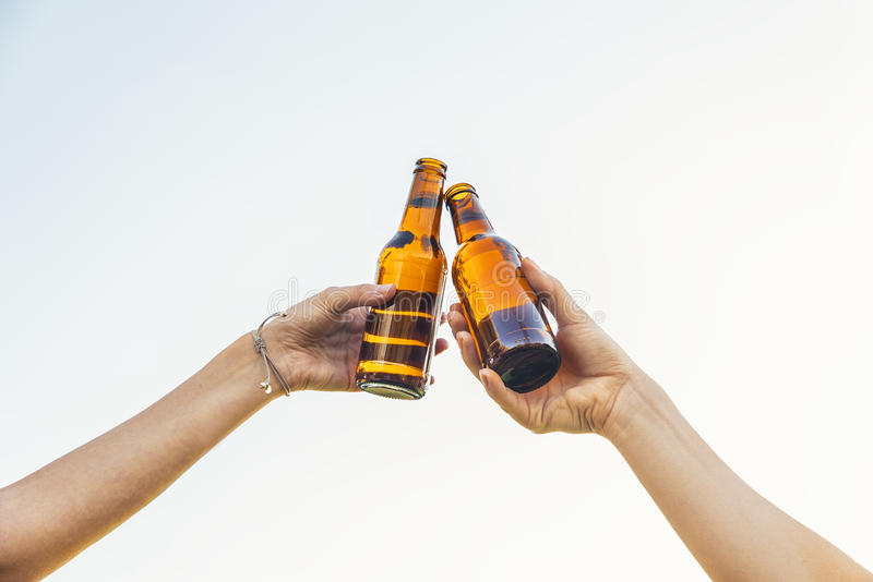 Garrafas fêmeas do tinido do elogio dos amigos da cerveja nas mãos foto de stock royalty free