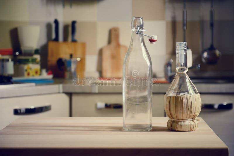 Garrafas na tabela de madeira no fundo da cozinha foto de stock