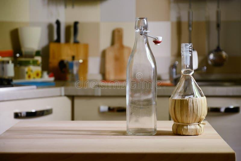 Garrafas na tabela de madeira no fundo da cozinha foto de stock royalty free