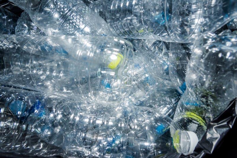 Garrafas plásticas nos sacos de lixo pretos que esperam para ser tomado para reciclar imagens de stock