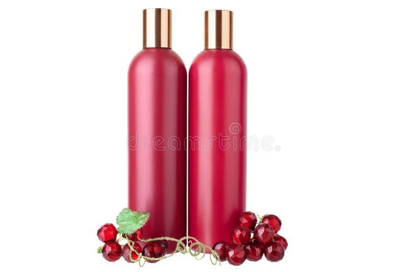 Garrafas plásticas vermelhas do condicionador do champô dois e de cabelo, gel do chuveiro e loção hidratando fundo branco no clos imagens de stock