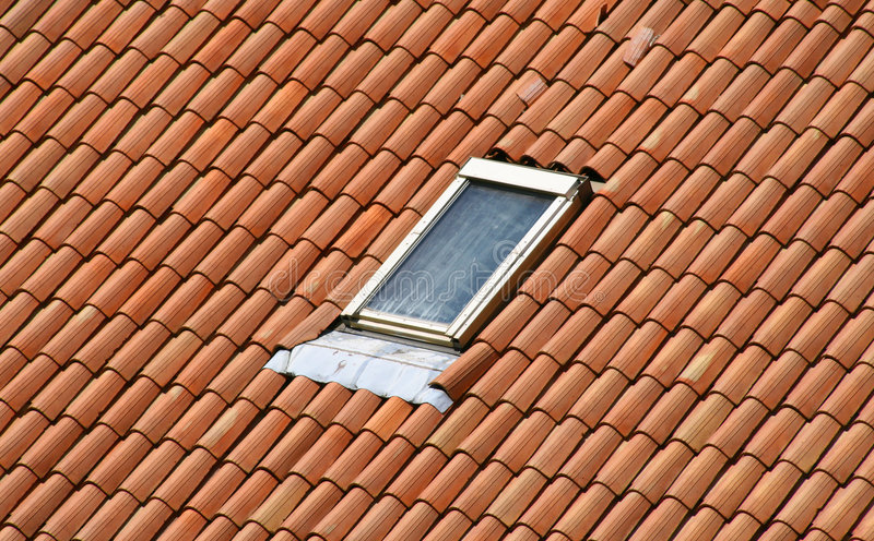 Garret on a roof. A classic style roof with red Tiles and a garret royalty free stock photography