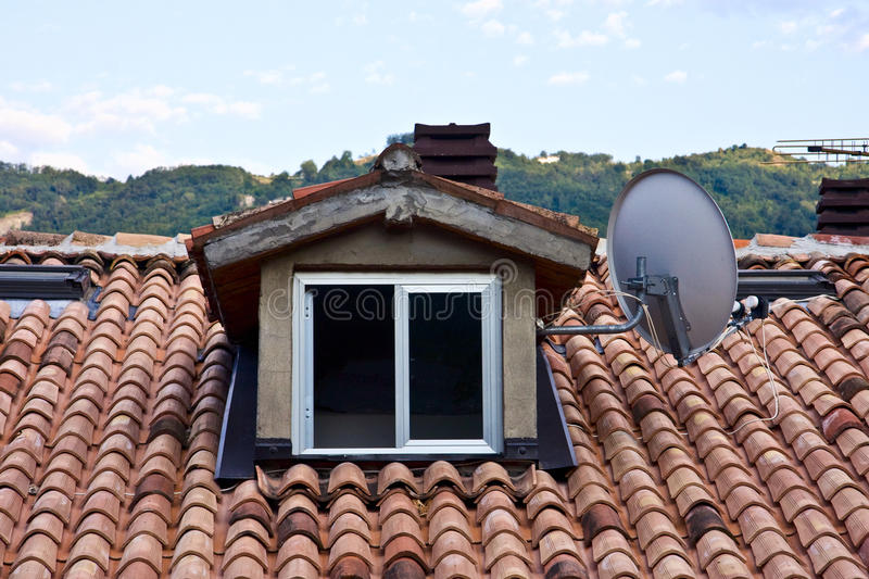 The garret and the roof tiles. With the satellite dish on the roof of a house and the surrounding hills in the background stock photo