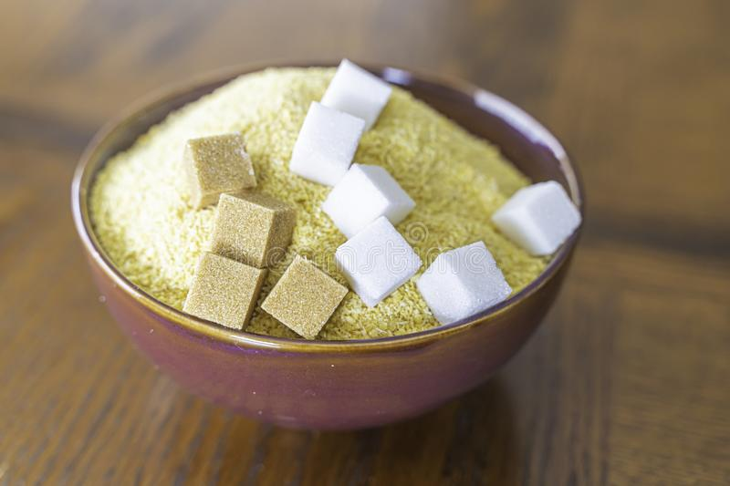 Garri with brown and white Sugar cubes a popular Nigerian Snack. Garri and Sugar a popular Nigerian Snack - Drink Garri stock photo