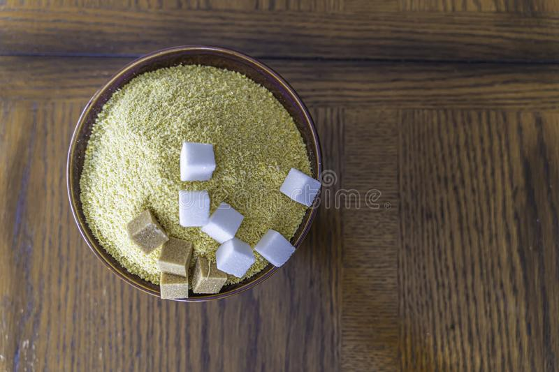 Garri with brown and white Sugar cubes a popular Nigerian Snack. Garri and Sugar a popular Nigerian Snack - Drink Garri stock images