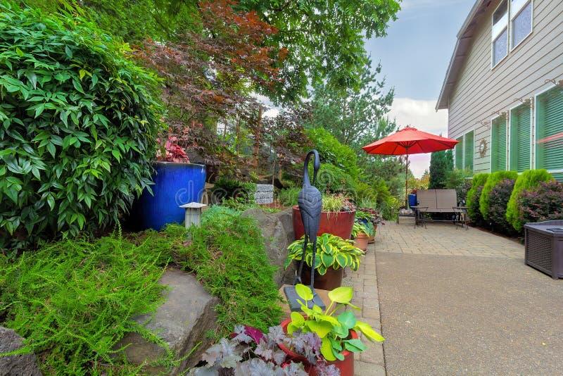 Garten-Hinterhof mit Patio-Sitzplätzen und Regenschirm lizenzfreie stockfotos