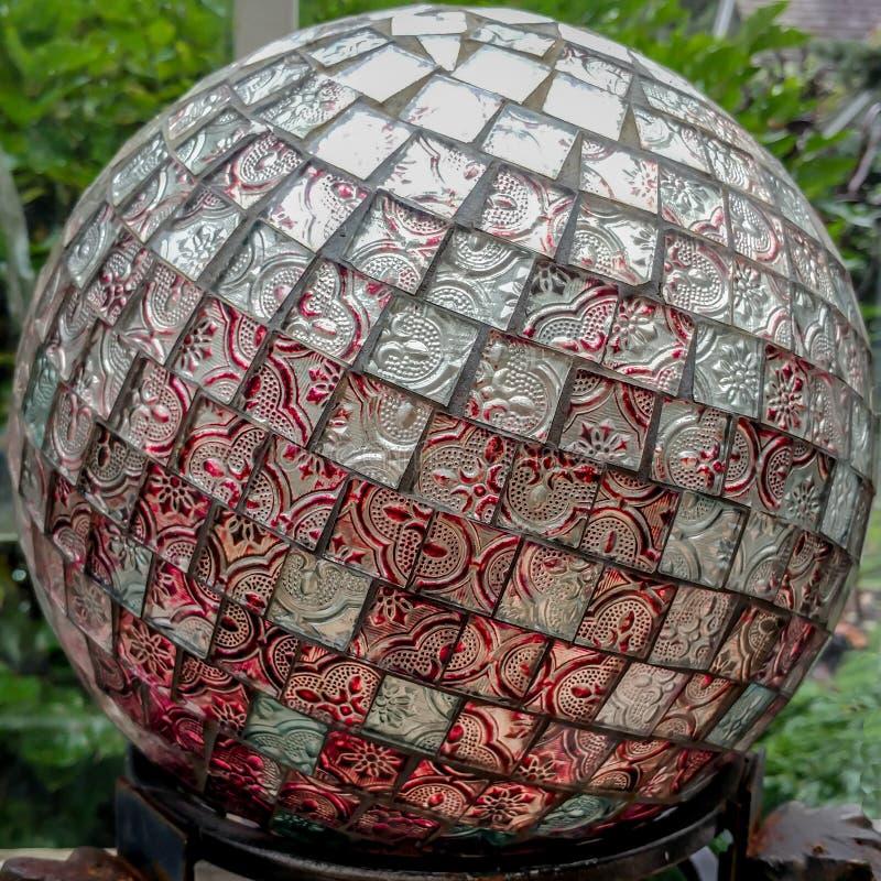 Garten-Kugel mit den roten und silbernen Fliesen auf einem Bereich stockbilder