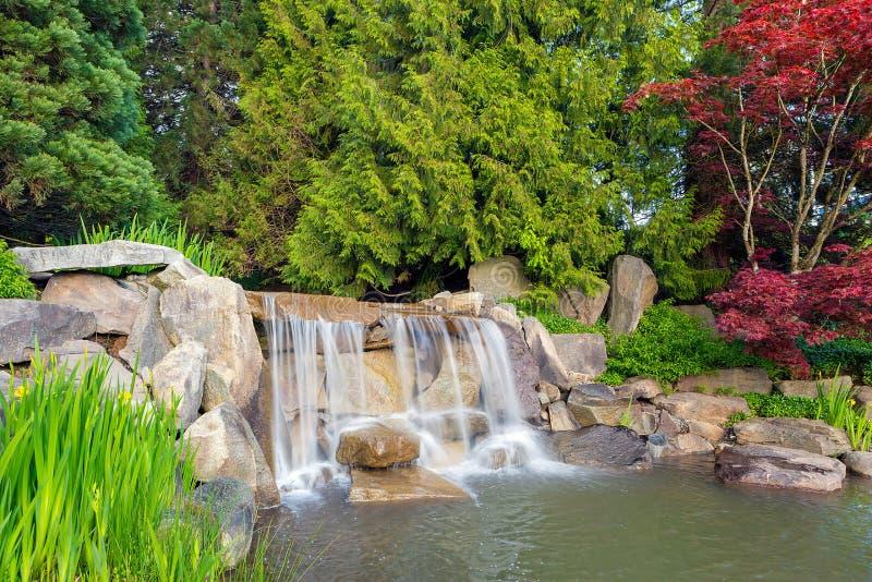 Garten-Landschaft mit Wasserfall und Bäumen stockbild