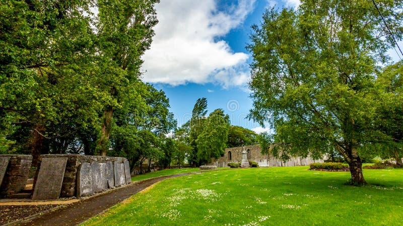 Garten mit grünem Gras, Bäumen und einem Weg in Abbey Graveyard im Dorf von Athlone stockfotografie