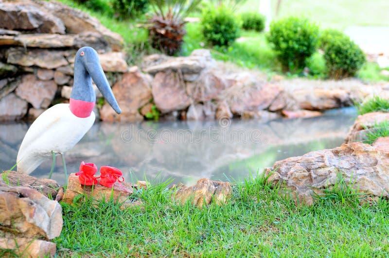 Garten mit Teich und künstlichem Vogel stockbilder