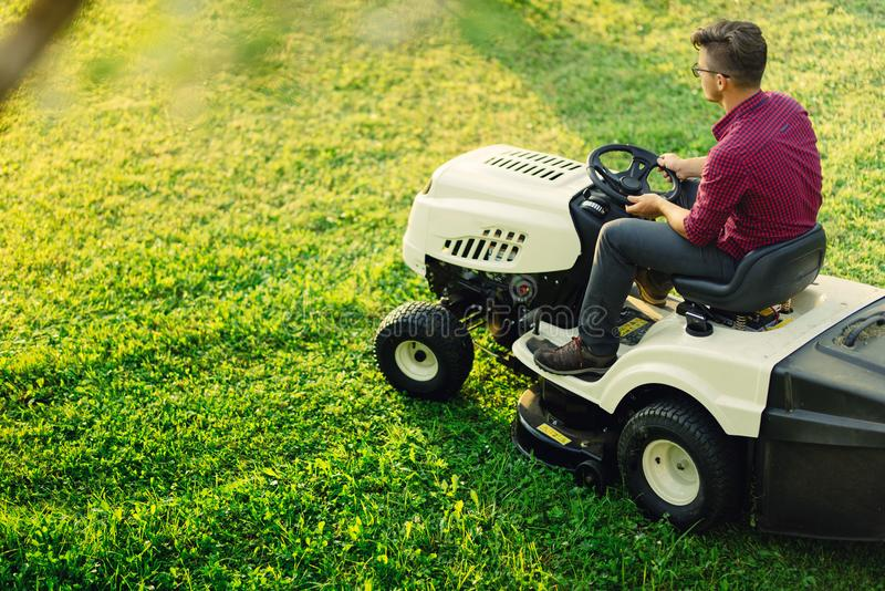 Gartenarbeit mit jungem männlichem Ausschnittgras Industrieller Rasenmäher in der Aktion lizenzfreies stockfoto