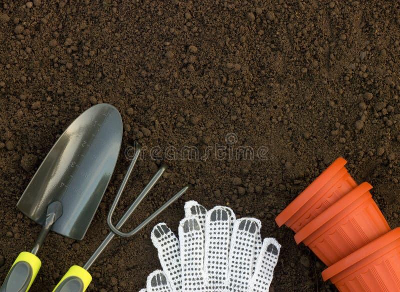 Gartenarbeit- und Keimungskonzept Schaufel, Rührstange, Handschuhe und Fluss lizenzfreies stockbild