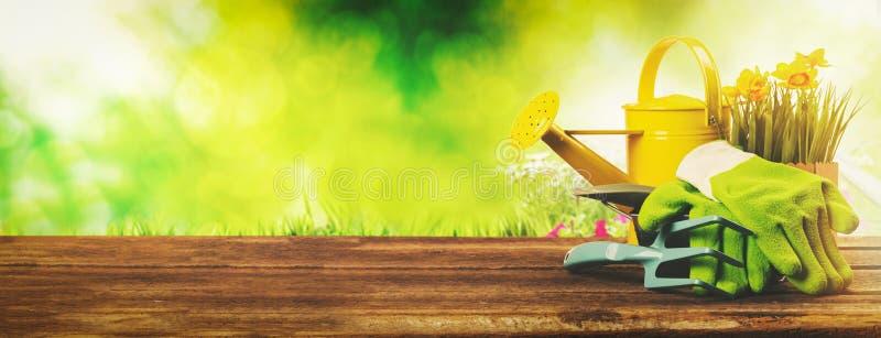 Gartenarbeitfahne - Gärtnerwerkzeuge auf grünem Gartenhintergrund stockfotos