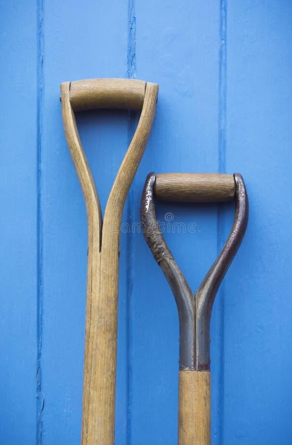 Gartenarbeitwerkzeug behandelt das Stillstehen gegen eine gemalte hölzerne blaue Tür lizenzfreies stockfoto