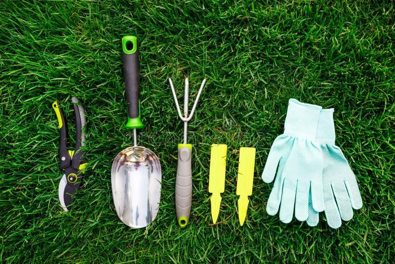 Gartenarbeitwerkzeug- und -ausrüstungsabschluß oben auf dem grünes Gras-, Gartenpflege- und Hobbykonzept lizenzfreie stockfotos