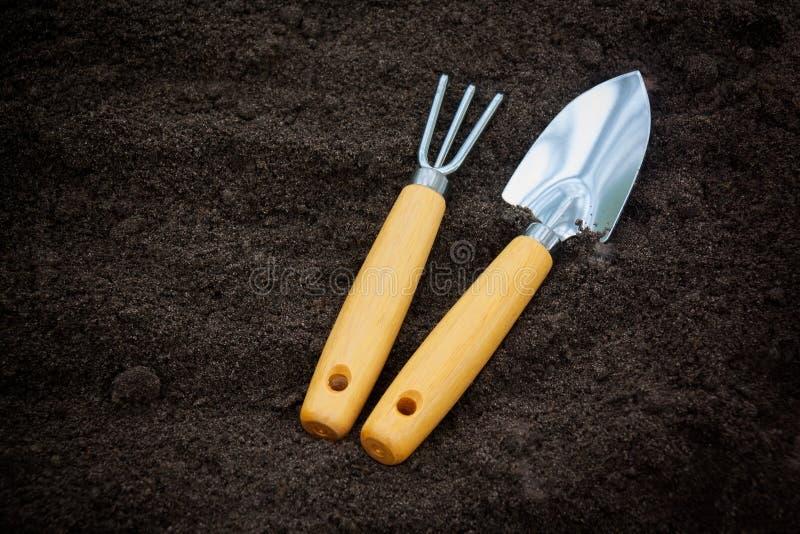 Gartenarbeitwerkzeuge auf einfachem Boden Hintergrund mit reichlichem Kopienraum lizenzfreie stockfotografie