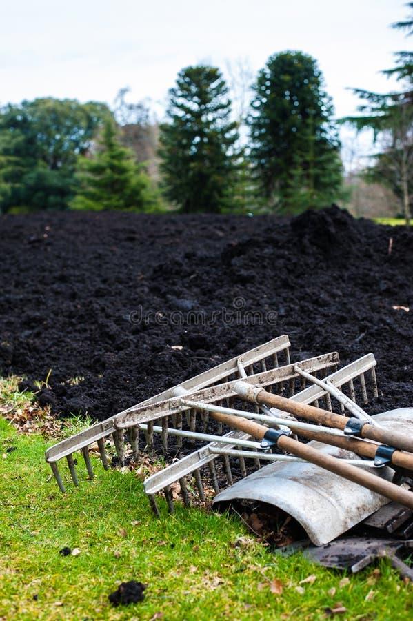 Gartenarbeitwerkzeuge, die auf einem Frühlingsrasen mit frisch digged Compo liegen stockbild
