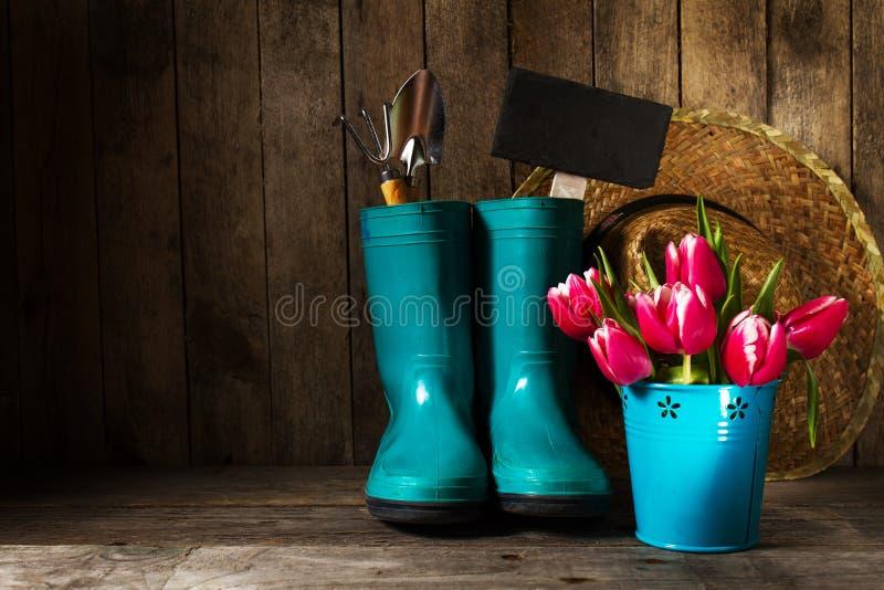 Gartenarbeitwerkzeuge mit blauen Gummistiefeln, Strohhut, Frühlingsblume stockbilder