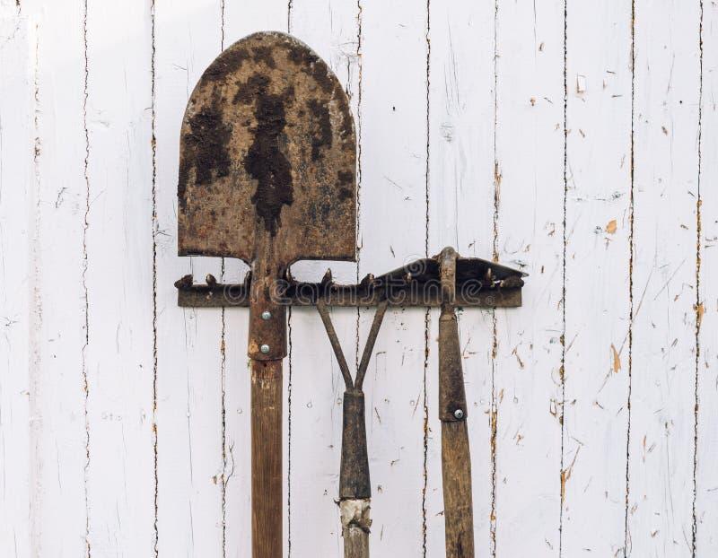 Gartenarbeitwerkzeuge nahe einer Wand lizenzfreie stockfotos