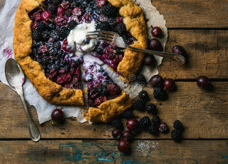 Gartenbeere crostata süße Torte mit geschmolzener Vanilleeisschaufel stockbild