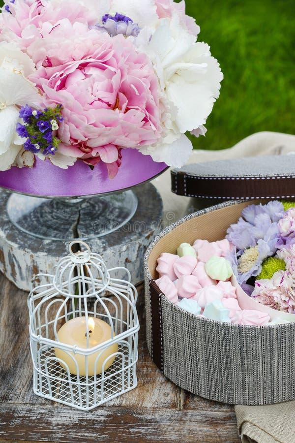 Gartenfesttabelle: Kasten Bonbons und Blumenstrauß von Blumen stockfotografie