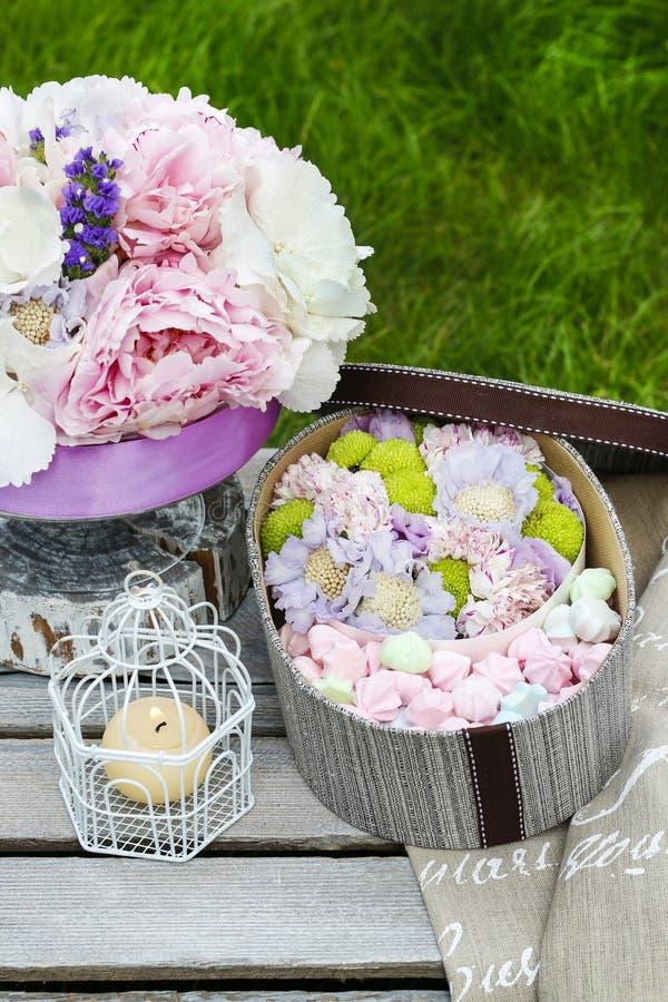 Gartenfesttabelle: Kasten Bonbons und Blumenstrauß von Blumen lizenzfreies stockfoto