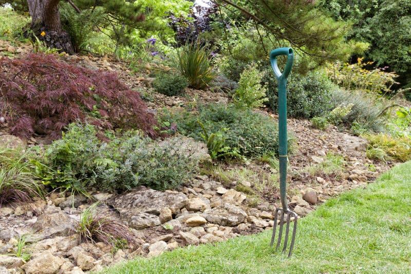 Gartengabel im Gras durch einen Rockery stockfoto