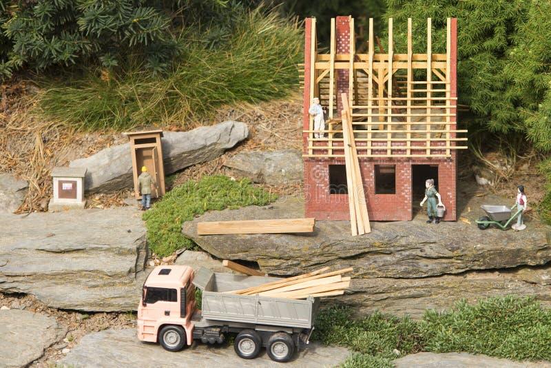 Gartenmodell einer Hausrekonstruktion mit Spielzeug stellt herum dar Neues Haus, das mit Holzarbeit für das Dach errichtet wird b stockfotos