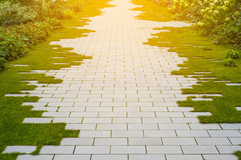 Gartenpflasterung - Kopfstein und Gras auf Bürgersteig stockbilder