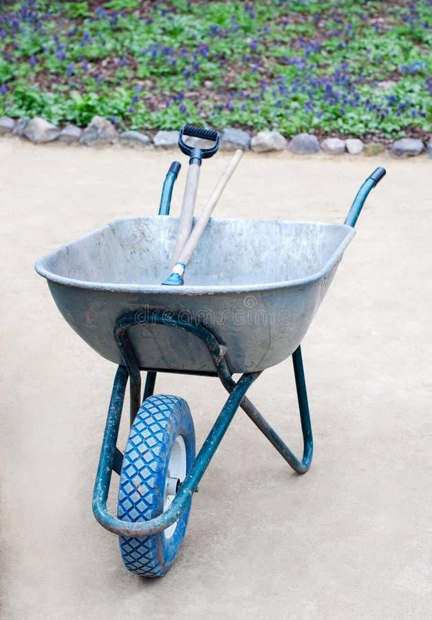 Gartenschubkarre mit blauem Rad und Gartenarbeitwerkzeugen nach innen stockfoto