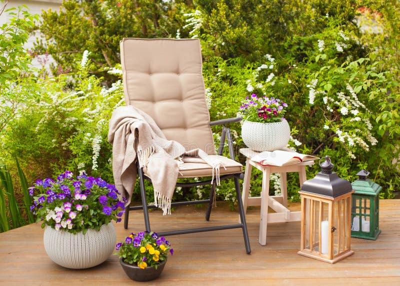 Gartenstuhl und -tabelle auf Terrasse blüht Busch lizenzfreies stockbild