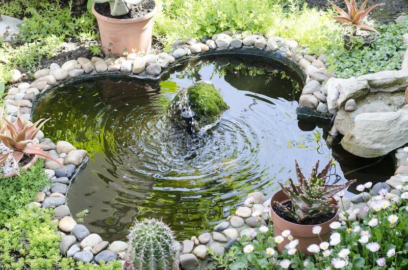 Gartenteich mit Brunnen lizenzfreie stockbilder