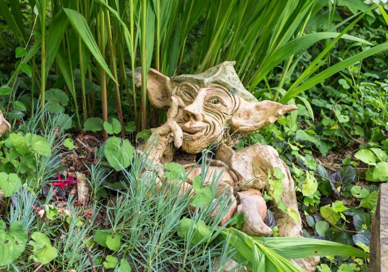 Gartenzwerg mit dem schelmischen denkenden Lächeln - Lehmzwerg im Garten stockfoto