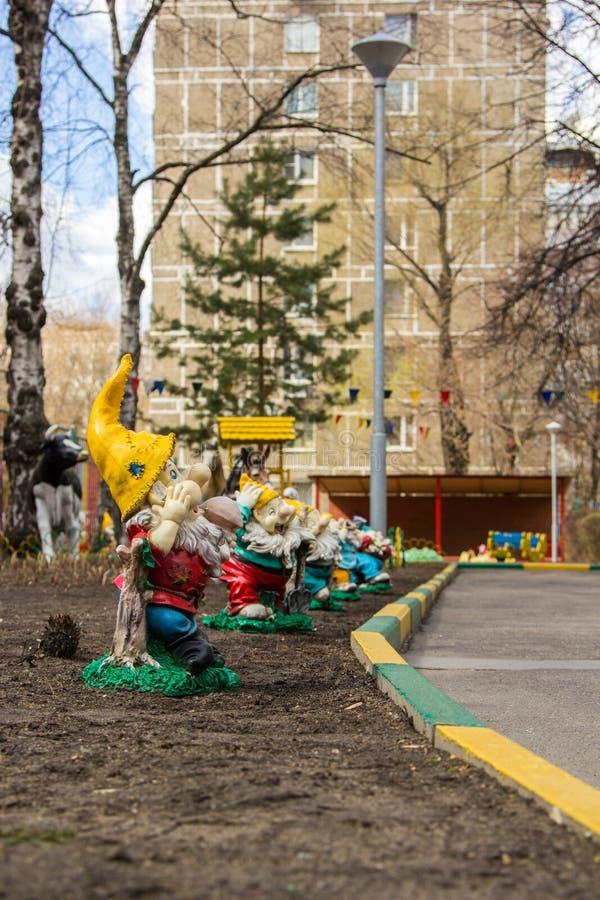 Gartenzwerge erscheint im Hof des Kindergartens stockbild