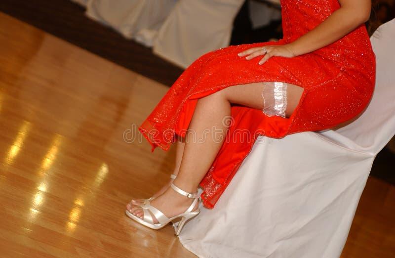 Garter on the bride`s leg red dress. Bride garter bride dresses garter on the leg. Picture of beautiful female barefoot legs royalty free stock photos