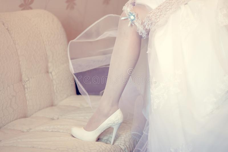 Garter at the foot of the bride. Bride in white stockings and wedding dress royalty free stock photos