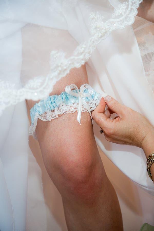 Garter on leg of bride. Hand fastening garter on leg of bride in traditional white wedding dress stock photos
