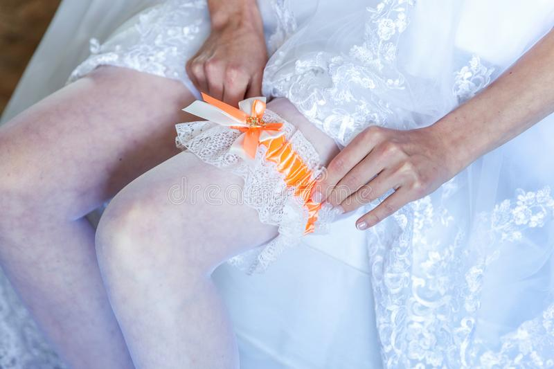 The bride putting on garter. Garter on the leg of a bride, slim bride in wedding luxury dress showing her silk garter. woman have a final preparation for wedding royalty free stock photos
