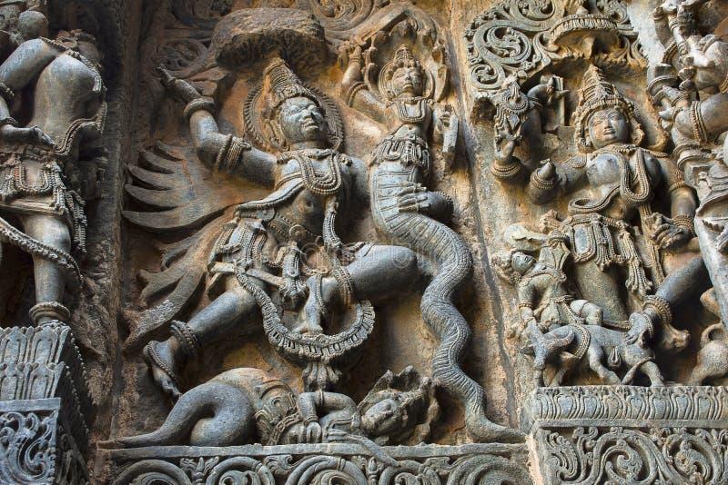 Garuda bestrijdt een paar slangen Het westenkant, Hoysalesvara-Tempel, Halebid stock fotografie