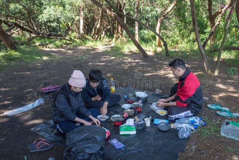 Garut, Индонезия - 12-ое августа 2018: Группа в составе молодые люди располагающся лагерем и варящ на горе Papandayan Гора Papand стоковая фотография rf