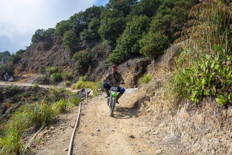 Garut, Индонезия - 12-ое августа 2018: Местное едет мотоцикл на горе Papandayan Гора Papandayan одно из стоковая фотография rf