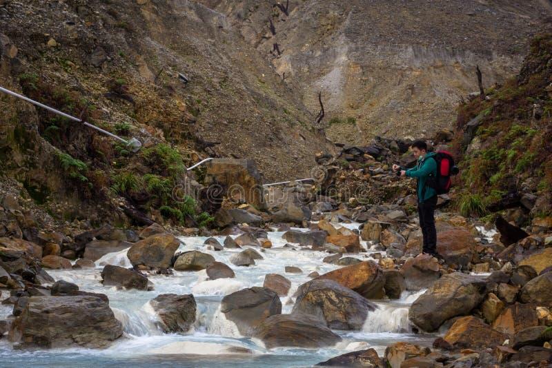 Garut Indonesien - Augusti 12, 2018: En man är tycka om och fotvandra det Papandayan berget Det Papandayan berget ?r ett av favor arkivfoto