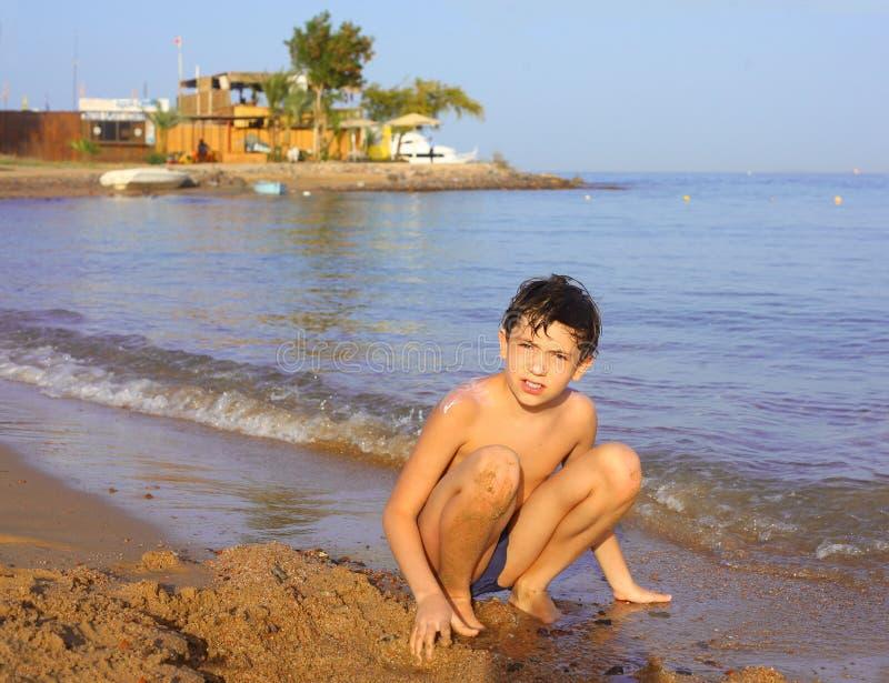 Garvad pojke för Preteen stilig sol på förälskelsen för Röda havetstrandwhrite arkivbilder